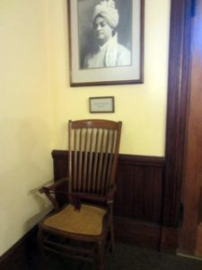 Photo of chair. Swami's photo is on the wall.